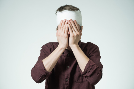 Miserable young man with bandage on his head closing face by hands. Image related with treatment of the wounds Stock Photo