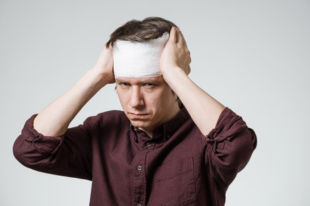 Poor young guy with bandage on his head putting hands on wound. Image related with treatment of the wounds Stock Photo