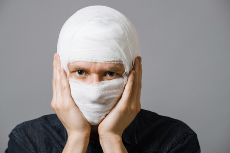 Injured young man with bandage all over his face putting hands on his cheeks. Image related with treatment of the wounds, plastic surgery, medical industry
