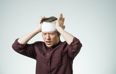 Poor young man with bandage on his head putting hands on temples. Image related with treatment of the wounds, medical industry Archivio Fotografico