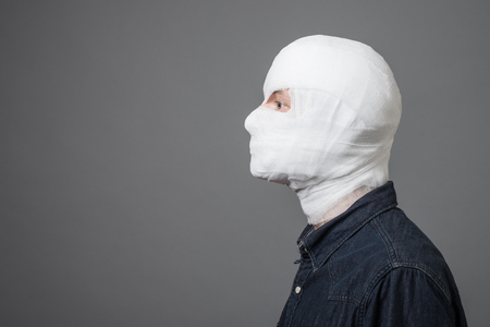 Injured young man after surgery with bandage all over his face with one eye opened. Image related with treatment of the wounds, plastic surgery, medical industry