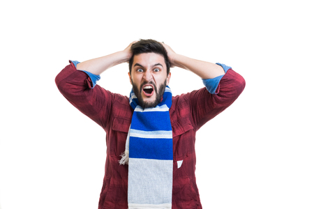 Crazy young bearded sport fan with white-blue color scarf tied on his neck showing his anger by lose