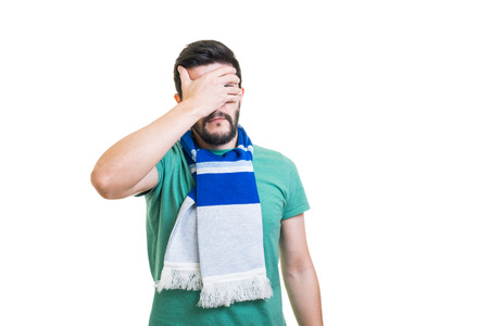Young bearded football fan with white-blue color scarf tied on his neck putting palm on his face