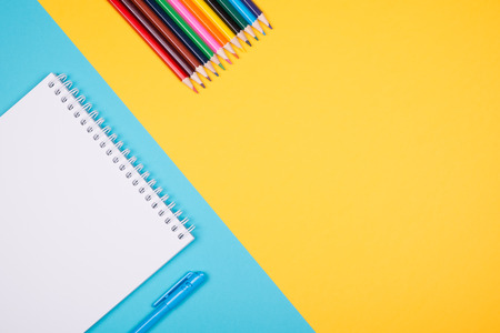 Empty notepad with blue pen on contrast and colorful pencils yellow and blue background