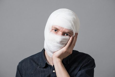 Injured young man with bandage all over his face putting hand on his cheek. Image related with treatment of the wounds, plastic surgery, medical industry