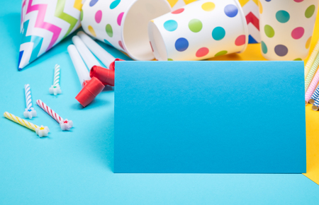 Set of birthday party items on contrast light blue and yellow surface view from above