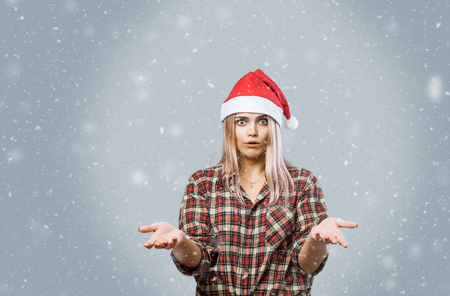 Young pretty woman in red christmas hat amazed