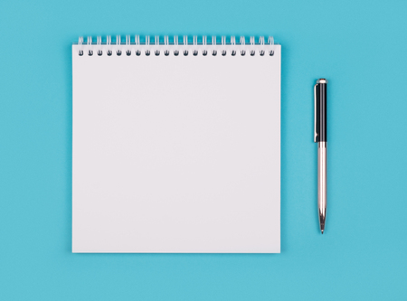 Opened empty white notepad on blue background. Shot from top point of view with copy space Stock Photo
