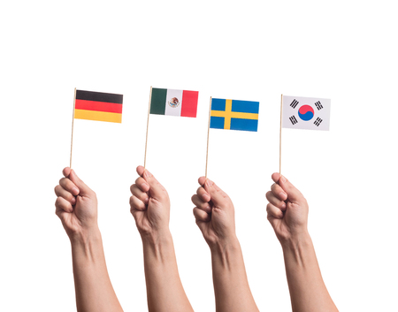 Little paper national flags in hands isolated on white background. Flags of national football teams of Germany, Mexico, Sweden, South Korea. World cup competitors in group F