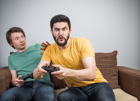 Two young friends playing awesome video games sitting on sofa and holding gamepads. Tourney or tournament concept