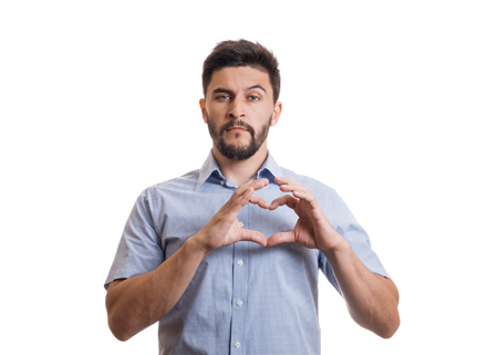 Young black haired handsome guy with beard in blue casual shirt showing heart shape symbol by hands isolated on white background. Saint Valentine day concept
