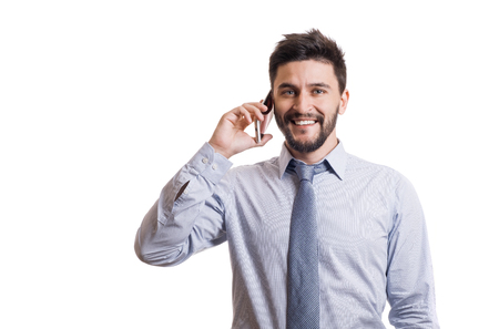 Young smiling businessperson with beard in blue classic shirt and tie having phone call on his smartphone against white background