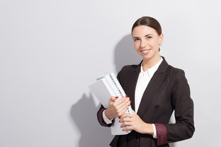 Young smiling businesswoman holding books in her hands. Fashion style photoshoot with har light source