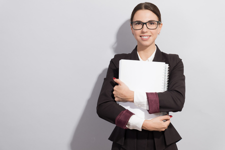 Young smiling businesswoman in glasses holding books in her hands. Fashion style photoshoot with har light source