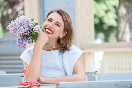 Outdoor portrait of young charming woman in light blue dress sitting at table of summer cafe with bouquet of fresh lilac and red sunglasses on it 版權商用圖片