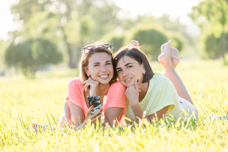 Outdoor portrait of two cheerful girls lying on lawn, using smartphone and spending good time together in park at sunny day. Standard-Bild