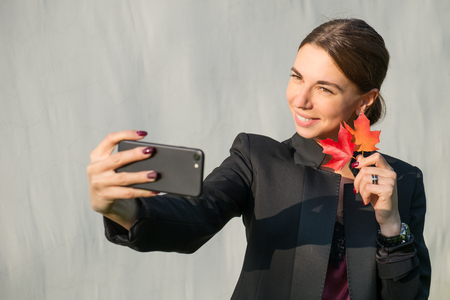 Young cheerful woman with autumn golden orange and red maple leaves taking selfie