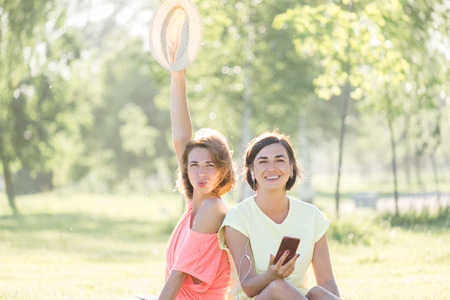 Two handsome girls, laughing sitting on lawn and listening music on smartphone together in green park at sunny warm day. Outdoor time spending in summer day Standard-Bild