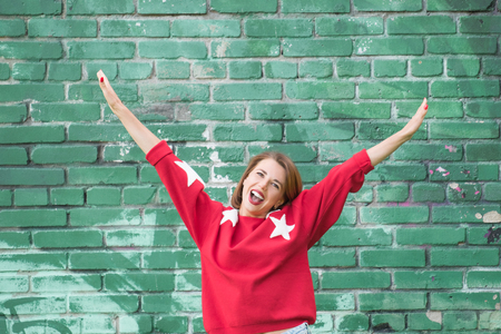 Young charming smiling girl in red sweater with stars posing against green brick wall as background Standard-Bild