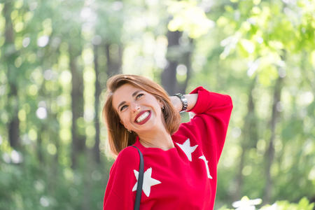 Young handsome smiling girl in red sweater with stars posing in green park at sunny day