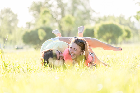 Two cute, laughing girls lying and rolling over grass on lawn in green park at sunny warm day. Outdoor time spending in summer day