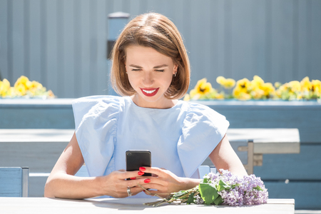 Outdoor portrait of young charming woman in light blue dress sitting at table of summer cafe and using smartphone  with bouquet of fresh lilac Standard-Bild