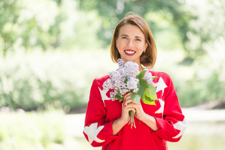 Young charming smiling girl in red sweater with stars holding bouquet of lilac posing in green park at sunny day Standard-Bild