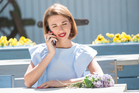 Outdoor portrait of young charming woman in light blue dress sitting at table of summer cafe and having conversation at smartphone  with bouquet of fresh lilac Standard-Bild