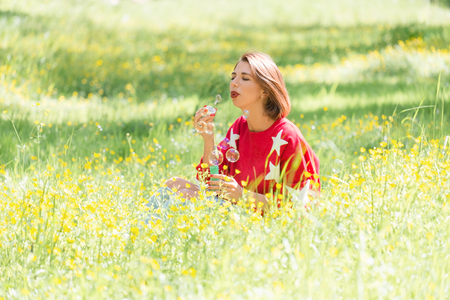 Young handsome girl sitting on grass and blowing soap bubbles in the air at sunny day in park