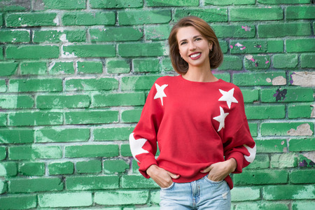 Young charming smiling girl in red sweater with stars posing against green brick wall as background 版權商用圖片