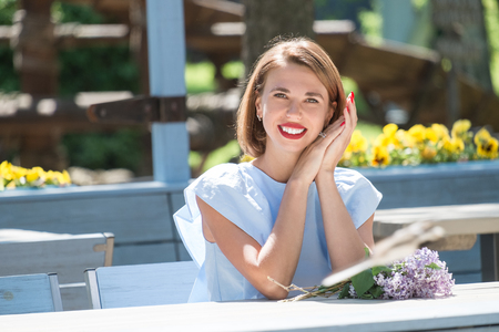 Outdoor portrait of young charming woman in light blue dress sitting at table of summer cafe with bouquet of fresh lilac