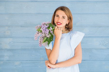 Beautiful portrait of young charming girl with bouquet of fresh lilac against blue wooden background