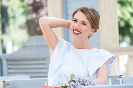 Outdoor portrait of young charming woman in light blue dress sitting at table of summer cafe with bouquet of fresh lilac and red sunglasses on it Standard-Bild