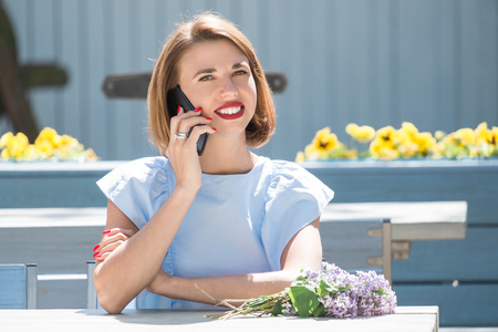 Outdoor portrait of young charming woman in light blue dress sitting at table of summer cafe and having conversation at smartphone  with bouquet of fresh lilac 版權商用圖片