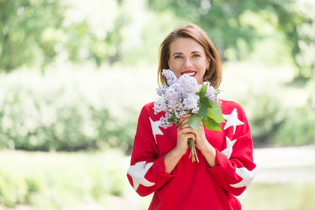 Young charming smiling girl in red sweater with stars holding bouquet of lilac posing in green park at sunny day 版權商用圖片