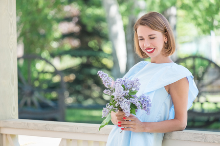 Beautiful portrait of young charming girl in light blue dress with bouquet of fresh lilac standing on terrace wooden cottage