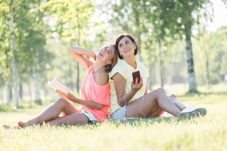 Two cheerful girls sitting on lawn, reading book, listening music on smartphone in green park at sunny warm day. Outdoor time spending in summer day Standard-Bild