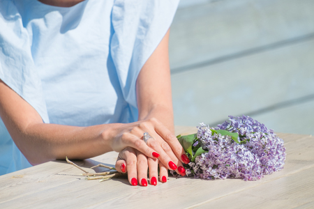 Bouquet of lilac in woman hands with red nails on wooden desk