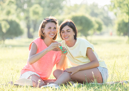 Outdoor portrait of two cheerful girls sitting on lawn and blowing soap bubbles in the air together in park at sunny day.