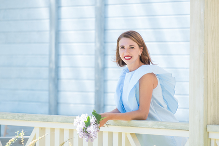 Beautiful portrait of young charming girl in light blue dress with bouquet of fresh lilac standing on terrace of blue wooden cottage Standard-Bild