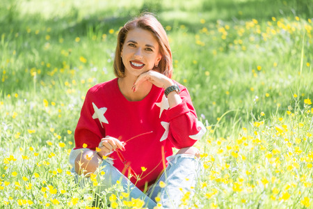 Young handsome girl sitting on grass in sunny day. Outdoor portrait of cheerful relaxed woman in red sweater in park