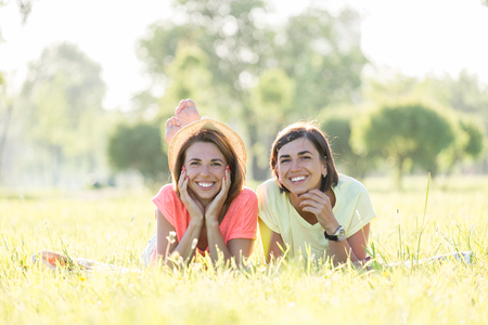 Two cute, laughing girls lying on lawn in green park at sunny warm day. Outdoor time spending in summer day