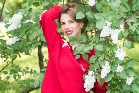 Young charming smiling woman in red sweater with stars standing in branches with white flowers in green park at sunny day