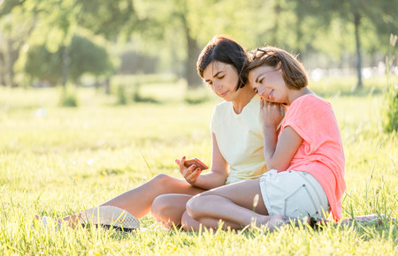 Outdoor portrait of two cheerful girls sitting on lawn, using smartphone and having good time together in park at sunny day.
