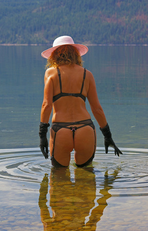 garter belt: A sexy woman fashion model wearing lingerie while posing in a lake