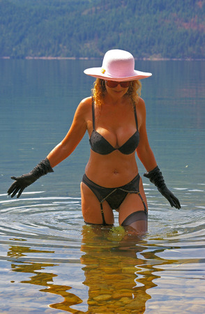garter belt: A sexy woman fashion model wearing lingerie while wading in a lake