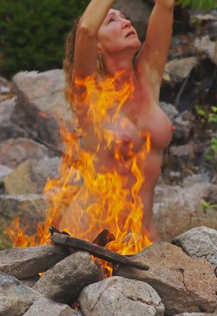 火の隣にセクシーな裸の女性モデルポーズ