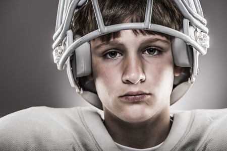 football teams: Youth football player wearing helmet, close-up Stock Photo