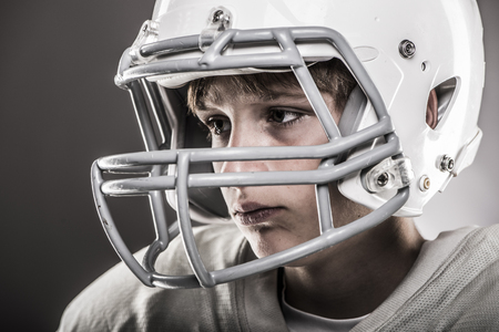 youth sports: Youth football player wearing helmet, close-up Stock Photo