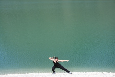 Young man stretching on beach Stock Photo - 10930233